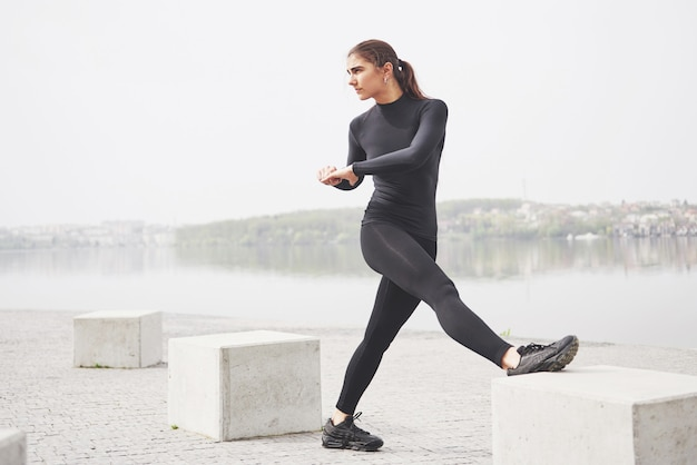 Une jeune femme fait du sport au bord d'un lac dans le parc