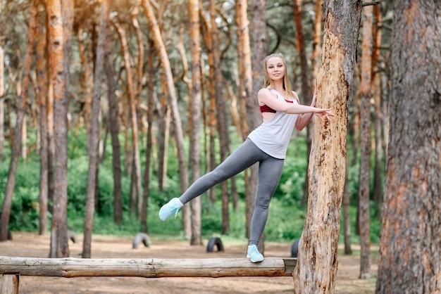 Une jeune femme fait du sport dans le parc parmi les arbres