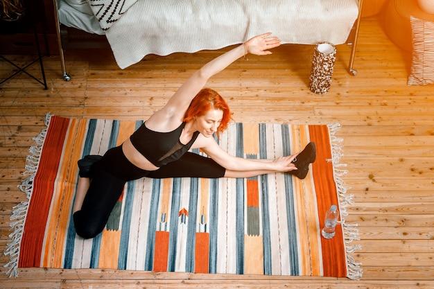 Une jeune femme fait du sport à la maison, entraînement en ligne. l'athlète s'étire, médite dans la chambre, à l'arrière-plan il y a un lit, un vase, un tapis.