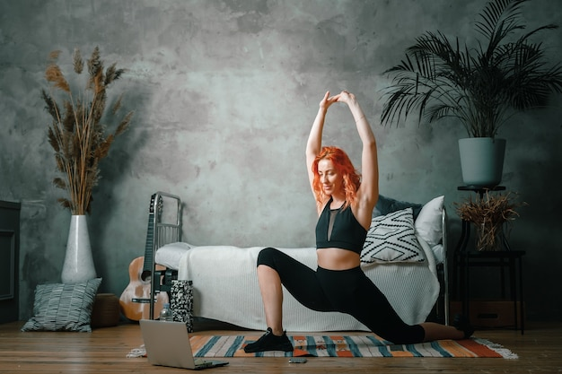 Une jeune femme fait du sport à la maison, entraînement en ligne