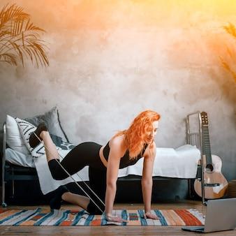 Une jeune femme fait du sport à la maison, s'entraîne en ligne. l'athlète balance sa jambe avec des élastiques de fitness sport