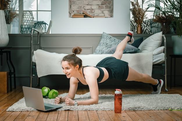 Jeune femme fait du sport à la maison, s'entraîne en ligne
