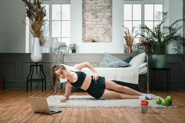 La jeune femme fait du sport à la maison. un sportif aux cheveux noirs fait une planche, regarde un film et étudie depuis un ordinateur portable sur un tapis dans la chambre