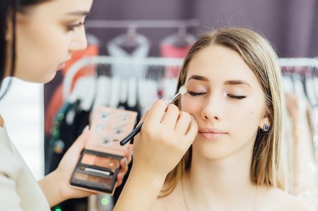 La jeune femme fait un maquillage naturel à un modèle