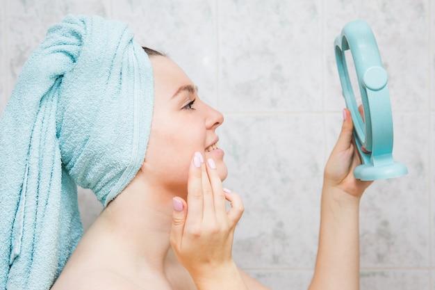 Jeune femme fait un massage du visage avec les mains dans la salle de bain.
