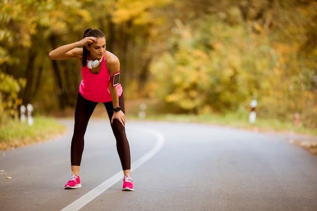 Jeune femme fait une pause pendant un entraînement dans la forêt d'automne