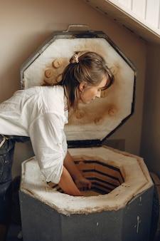 Jeune femme fait de la poterie en atelier