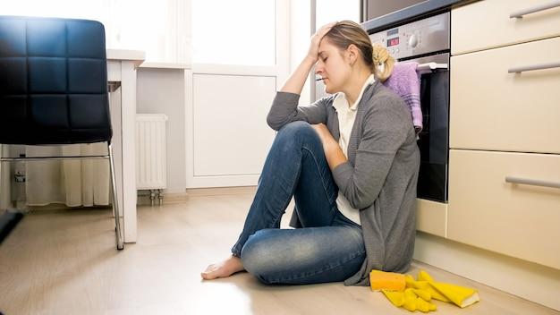 Jeune femme fatiguée assise sur le sol dans la cuisine après avoir fait des travaux ménagers.
