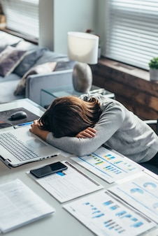 Jeune femme fatiguée dort au travail avec sa tête sur la table.