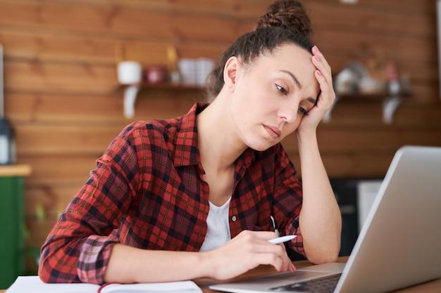 Jeune femme fatiguée essayant de se concentrer sur le réseautage tout en obtenant de nouvelles idées créatives pour un projet d'entreprise ou de conception