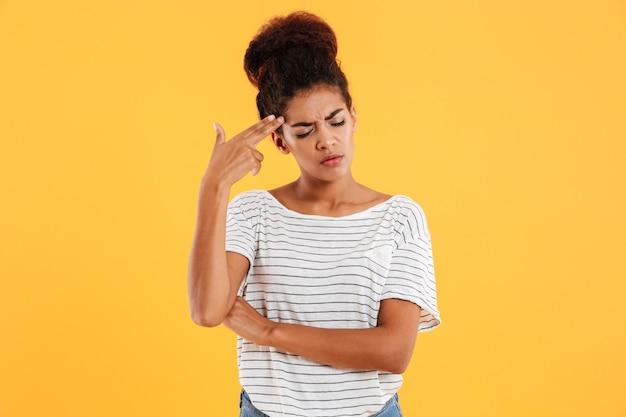 Jeune femme fatiguée faisant le geste du pistolet avec la main près de la tête