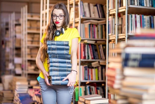Jeune femme fatiguée portant un tas de livres à l'ancienne bibliothèque
