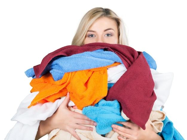 Jeune femme fatiguée portant des tas de vêtements différents