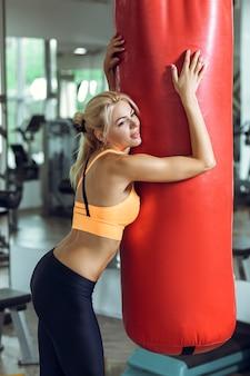 Jeune femme fatiguée s'entraînant avec un sac de boxe après s'être entraînée au gymnase