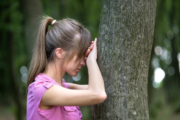 Jeune femme fatiguée se penchant sur un tronc d'arbre dans la forêt d'été.