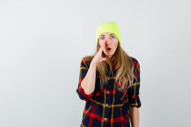 Jeune femme femme dans une chemise à carreaux avec un chapeau