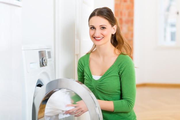 Jeune femme ou femme de ménage a la journée de lessive à la maison, elle sort la machine à laver ou la sécheuse