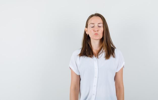Jeune femme fermant les yeux en se tenant debout en chemisier blanc et à la recherche de silence
