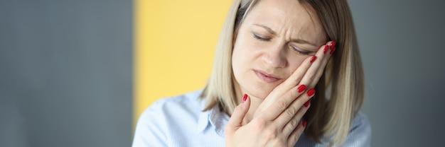 Jeune femme fermant les yeux et tenant la joue avec la main. aide avec le concept de maux de dents