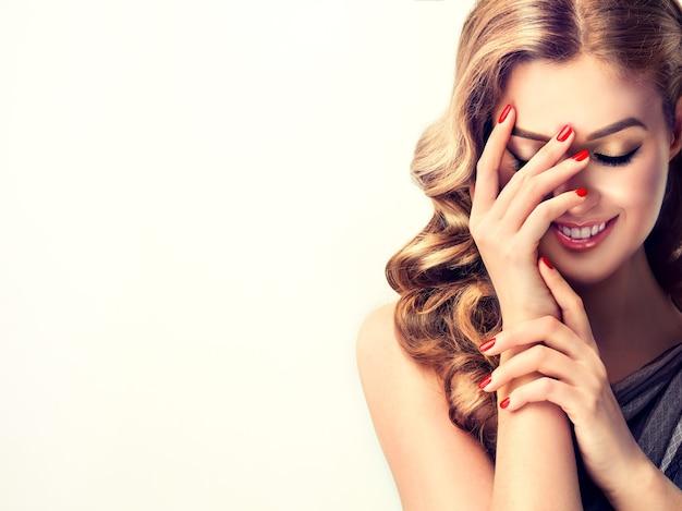 Jeune femme ferme le visage timide mais riant à la mainmaquillage parfait avec paupières dorées et manucure rouge à lèvres rouge sur les ongles