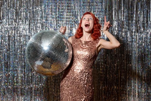 Jeune femme en fête avec boule disco sur des rideaux lumineux