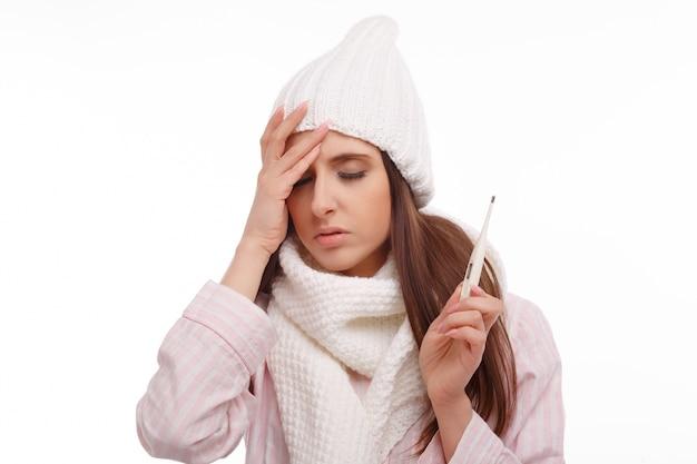 Jeune femme avec de la fièvre et la tenue d'un thermomètre