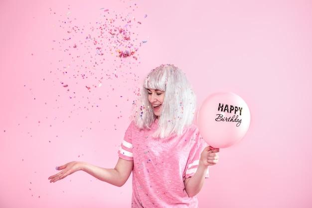 Jeune femme ou fille avec des ballons joyeux anniversaire. jette des confettis d'en haut. concept de vacances et de fête.