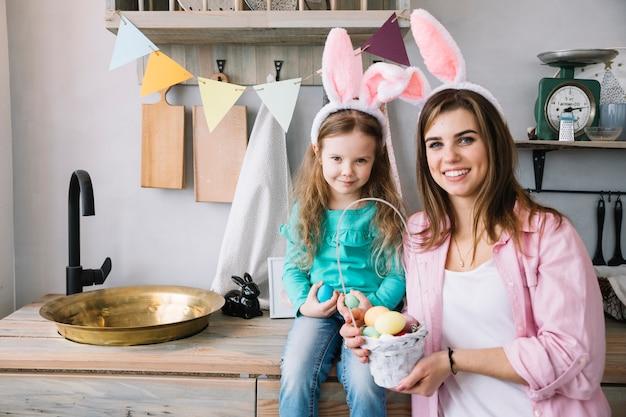 Jeune femme et fille debout avec panier d'oeufs de pâques