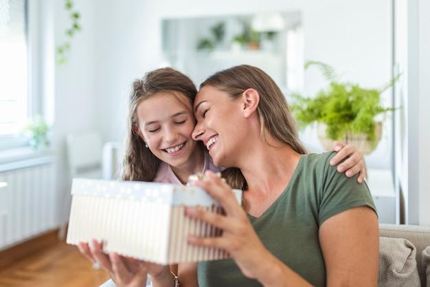 Jeune femme et fille à la maison célébrant la fête des mères assise sur un canapé fille embrassant la mère embrassant la joue maman riant joyeuse tenant une boîte-cadeau
