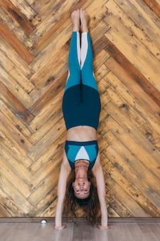Jeune femme fit faire des exercices de poirier près du mur.