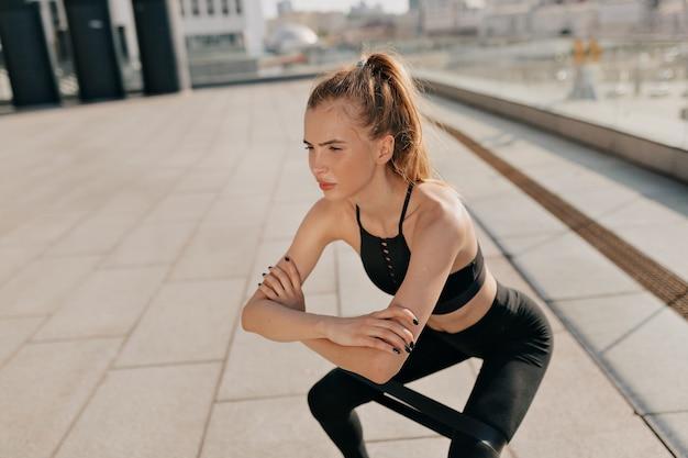 Jeune femme fit faire des squats avec une bande élastique de sport sur l'aire de jeux. photo de haute qualité