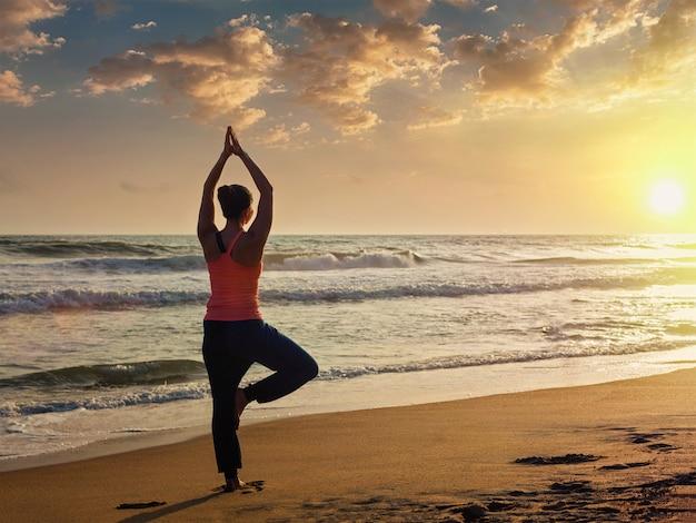 Jeune femme fit sportive faisant yoga arbre asana sur la plage