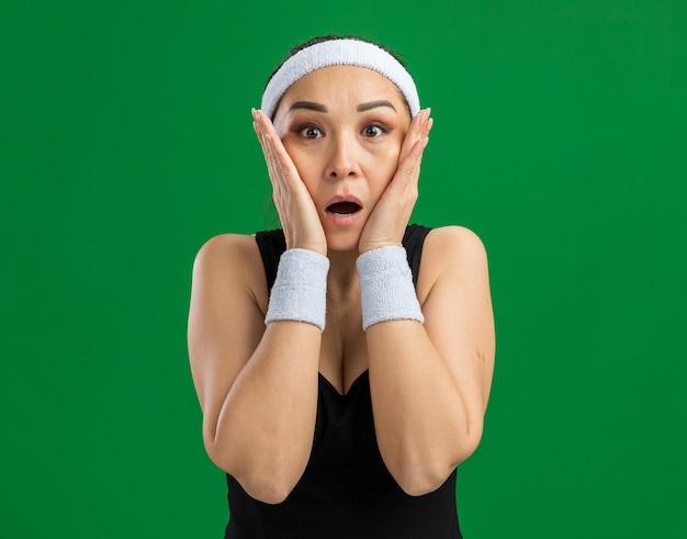 Jeune femme fitness avec bandeau et brassards étonnée et surprise debout sur un mur vert
