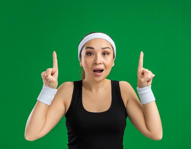 Jeune femme fitness avec bandeau et brassards surpris montrant des index debout sur un mur vert