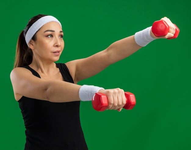 Jeune femme fitness avec bandeau avec haltères faisant des exercices tendus et confiants debout sur un mur vert