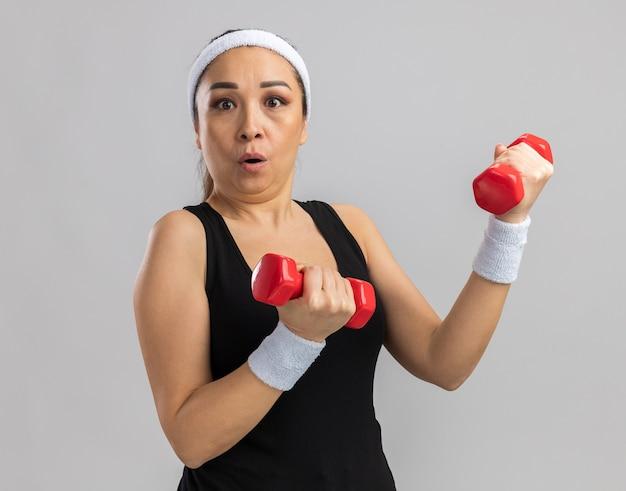 Jeune femme fitness avec bandeau tenant un haltère faisant des exercices confus et surpris debout sur un mur blanc