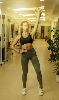 Jeune femme fitness faisant des exercices de développé couché avec kettlebell dans la salle de gym. entraînement fonctionnel avec poids libres
