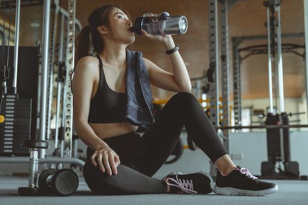 Jeune femme fitness fatiguée dans la salle de gym boire de l'eau fitness entraînement gym exercice mode de vie et sain