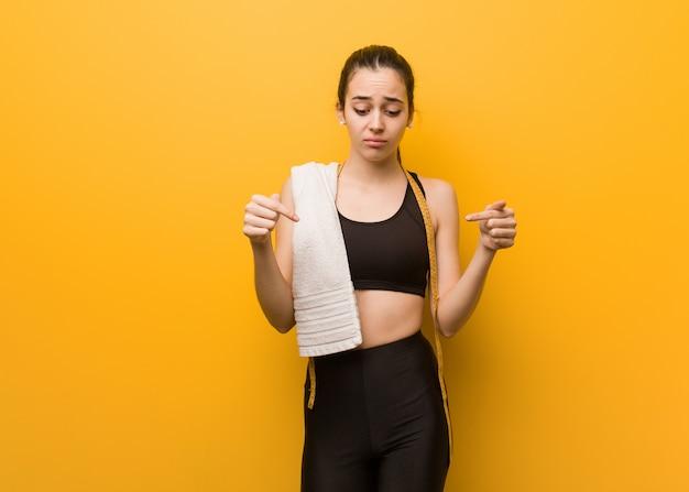 Jeune femme fitness pointant vers le bas