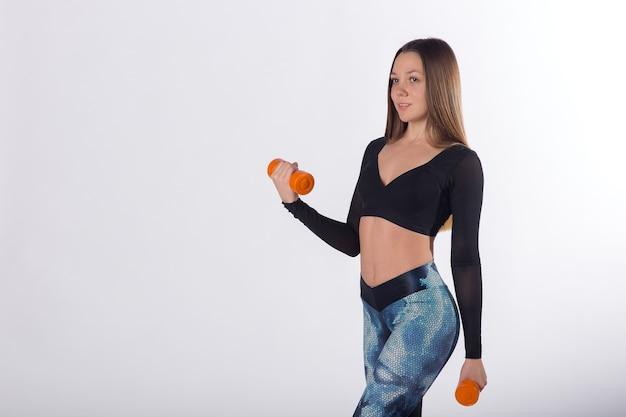 Jeune femme fitness sportswear exercices avec haltères, fond blanc