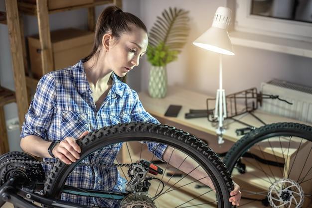 Jeune femme fixant un vélo de montagne dans un atelier. concept de préparation pour la nouvelle saison, réparation et entretien