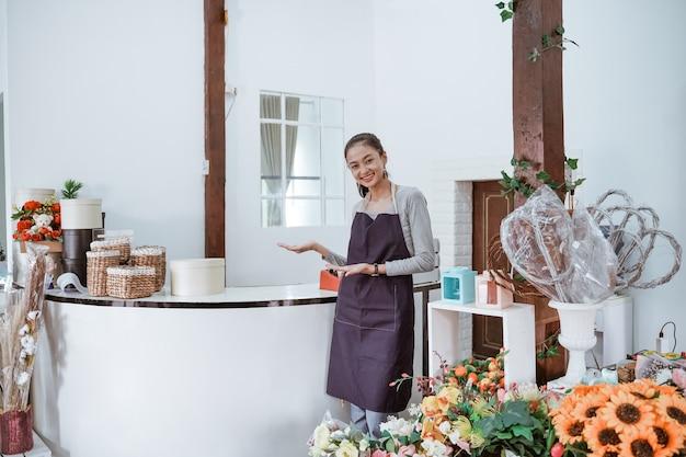 Jeune femme fleuriste portant un tablier debout devant le bureau souriant en regardant la caméra