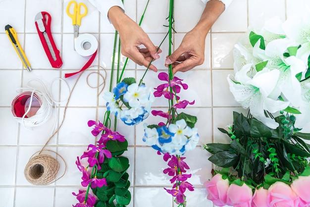 Jeune femme fleuriste travail faisant l'organisation de fleurs artificielles bricolage