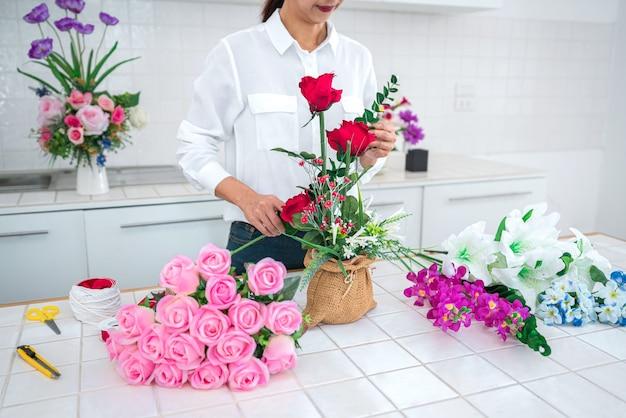 Jeune femme fleuriste travaillant en organisant des fleurs artificielles de bricolage, de l'artisanat et un concept fait à la main.