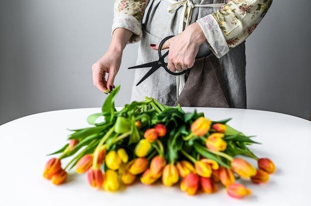 Jeune femme fleuriste travaillant avec des tulipes de fleurs fraîches, faisant bouquet