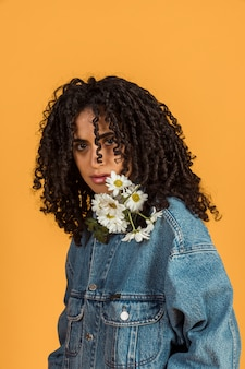 Jeune femme avec des fleurs au cou, regardant la caméra