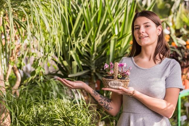 Jeune femme avec des fleurs dans un panier près de plantes vertes