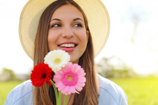 Jeune femme avec des fleurs de gerbera