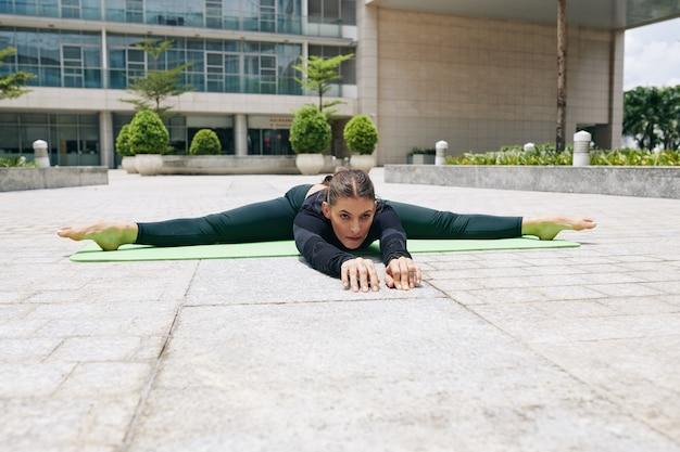 Jeune femme flexible faisant des divisions latérales et s'étendant vers l'avant lors de l'exercice à l'extérieur