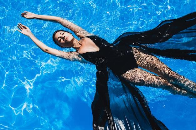 Jeune femme flottant sur l'eau sur son dos